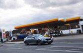 LT BMW 530e driving past petrol station