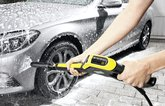 Person using Karcher pressure washer on car