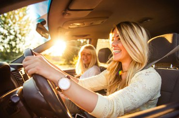 Women driving in sunshine