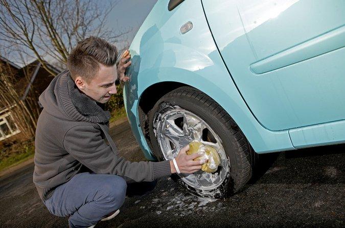 Man cleaning wheel