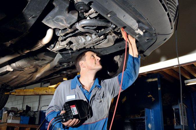 Man checking underside of car