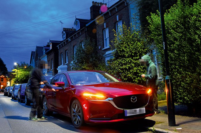 Two people attempting to break into a red Mazda 6
