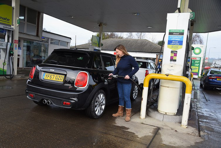 Woman re-fuelling Mini Cooper SD at petrol station