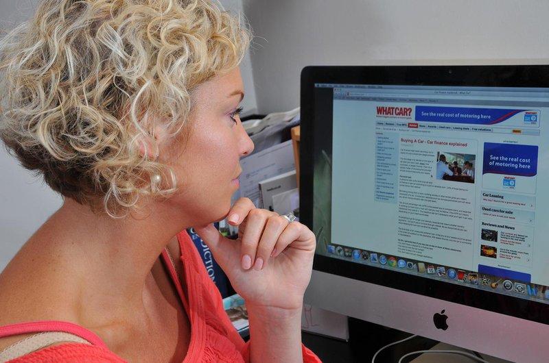 Lady at computer looking at What Car reviews