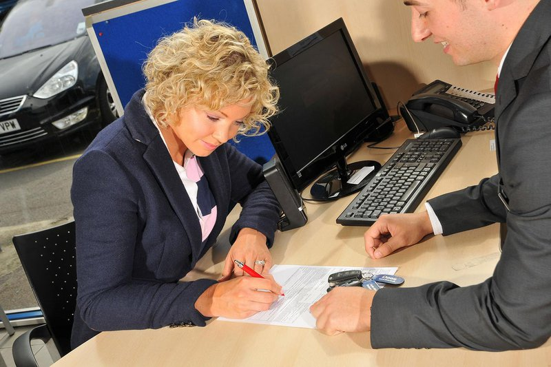 Lady signing car finance agreement in a showroom