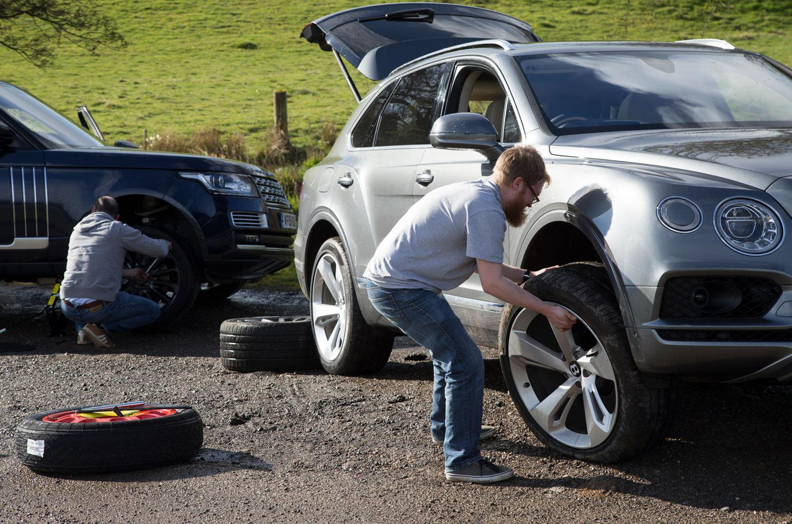 People changing wheels on cars