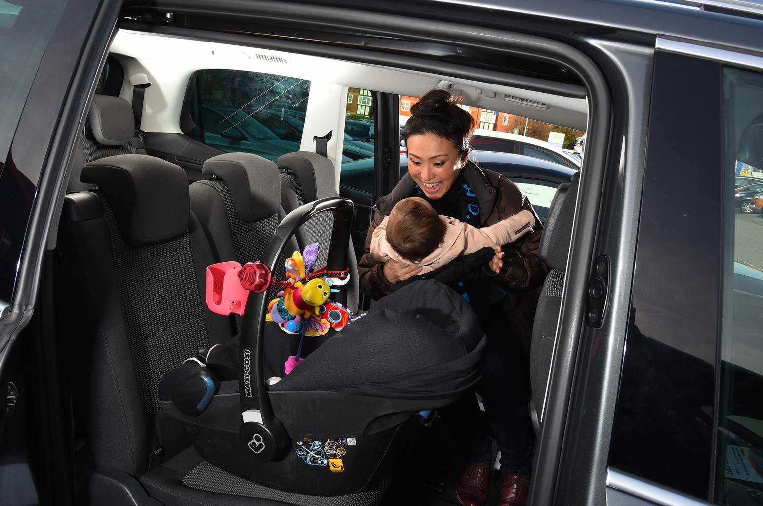 Lady putting baby into child car seat in car