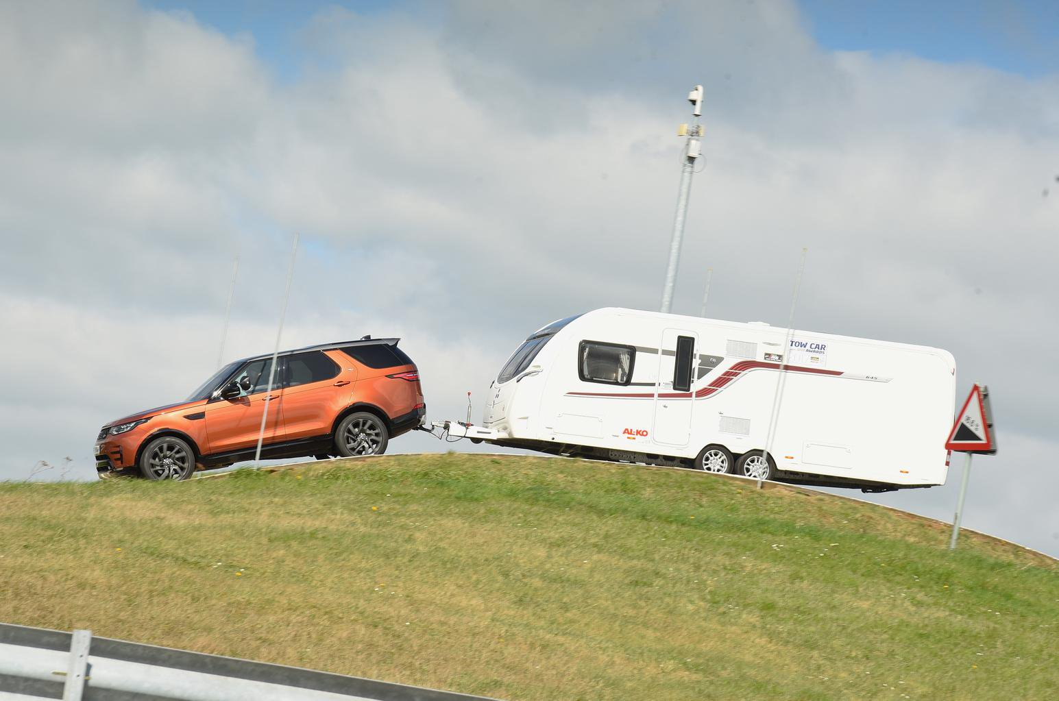 Land Rover discovery pulling caravan over hill