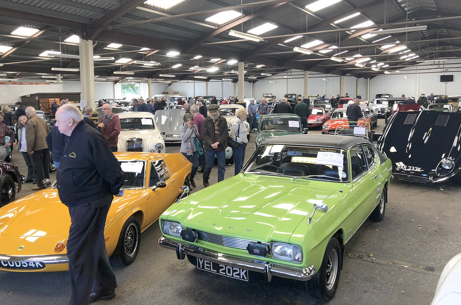 Potential bidders inspecting cars before auction commences