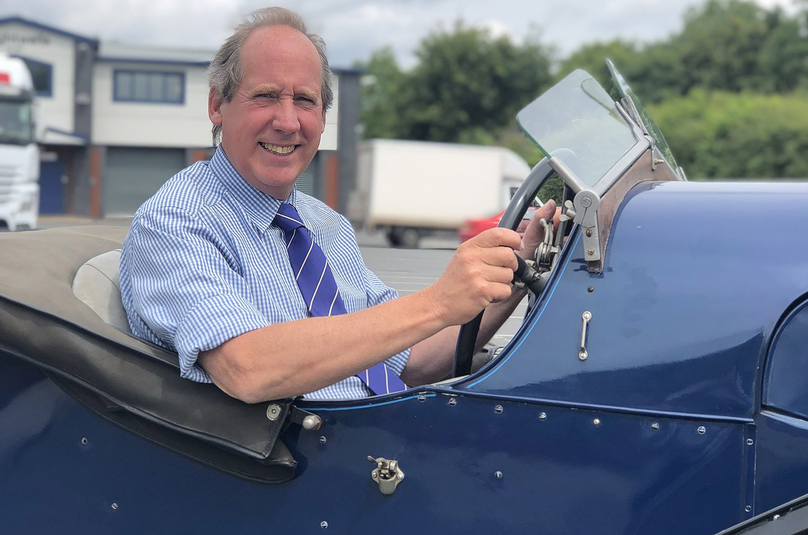 Man in blue shirt and tie sat in open top classic car
