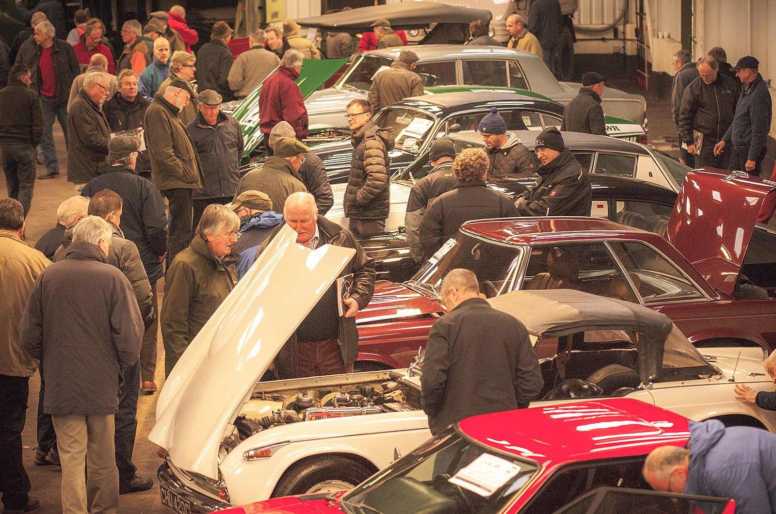 Potential bidders viewing classic cars before car auction commences