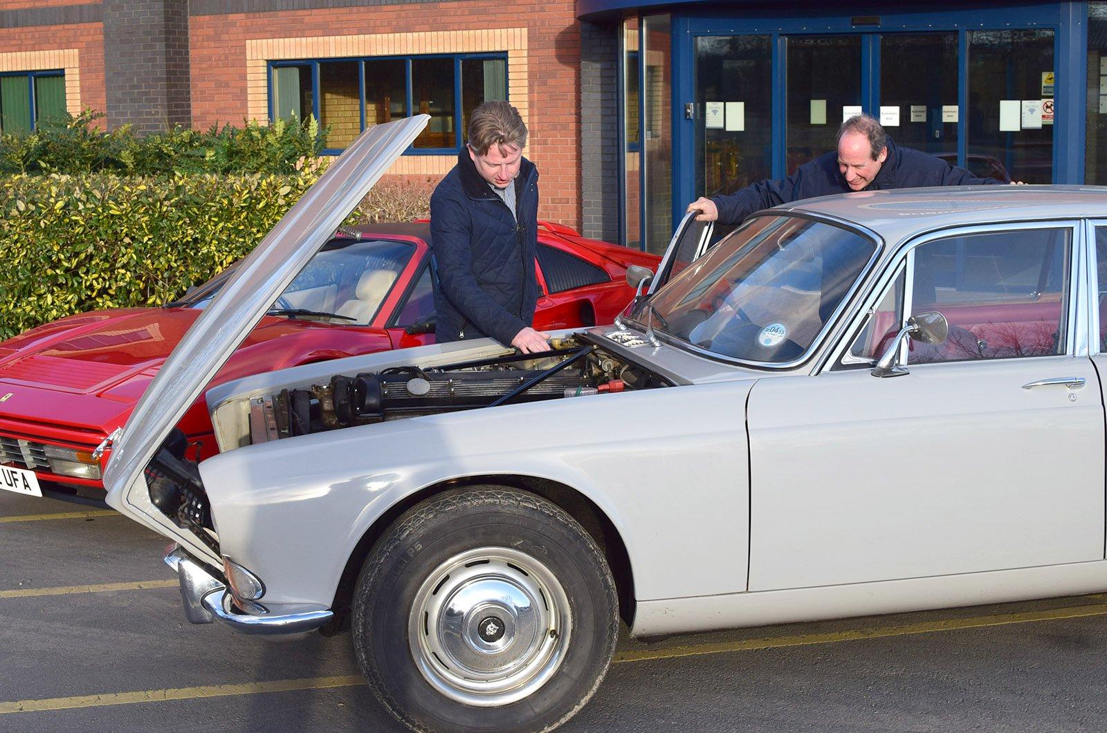 Man inspecting blue classic car