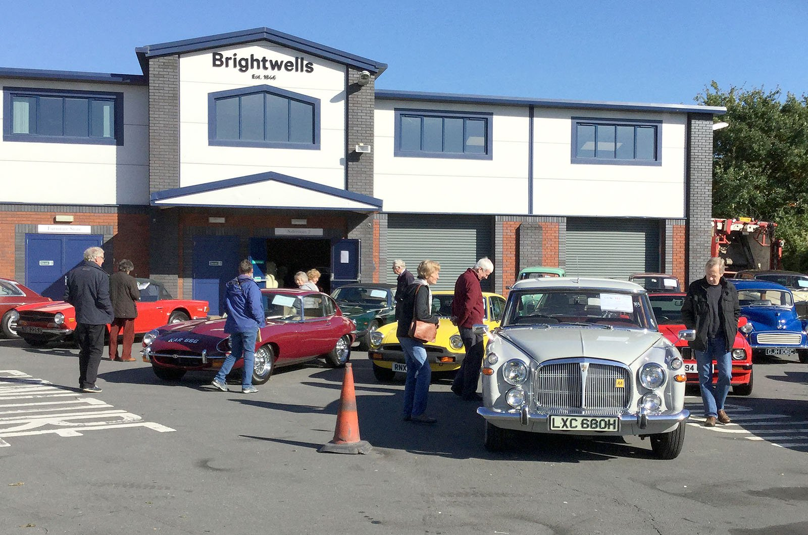 Potential bidders inspecting classic cars before auction commences