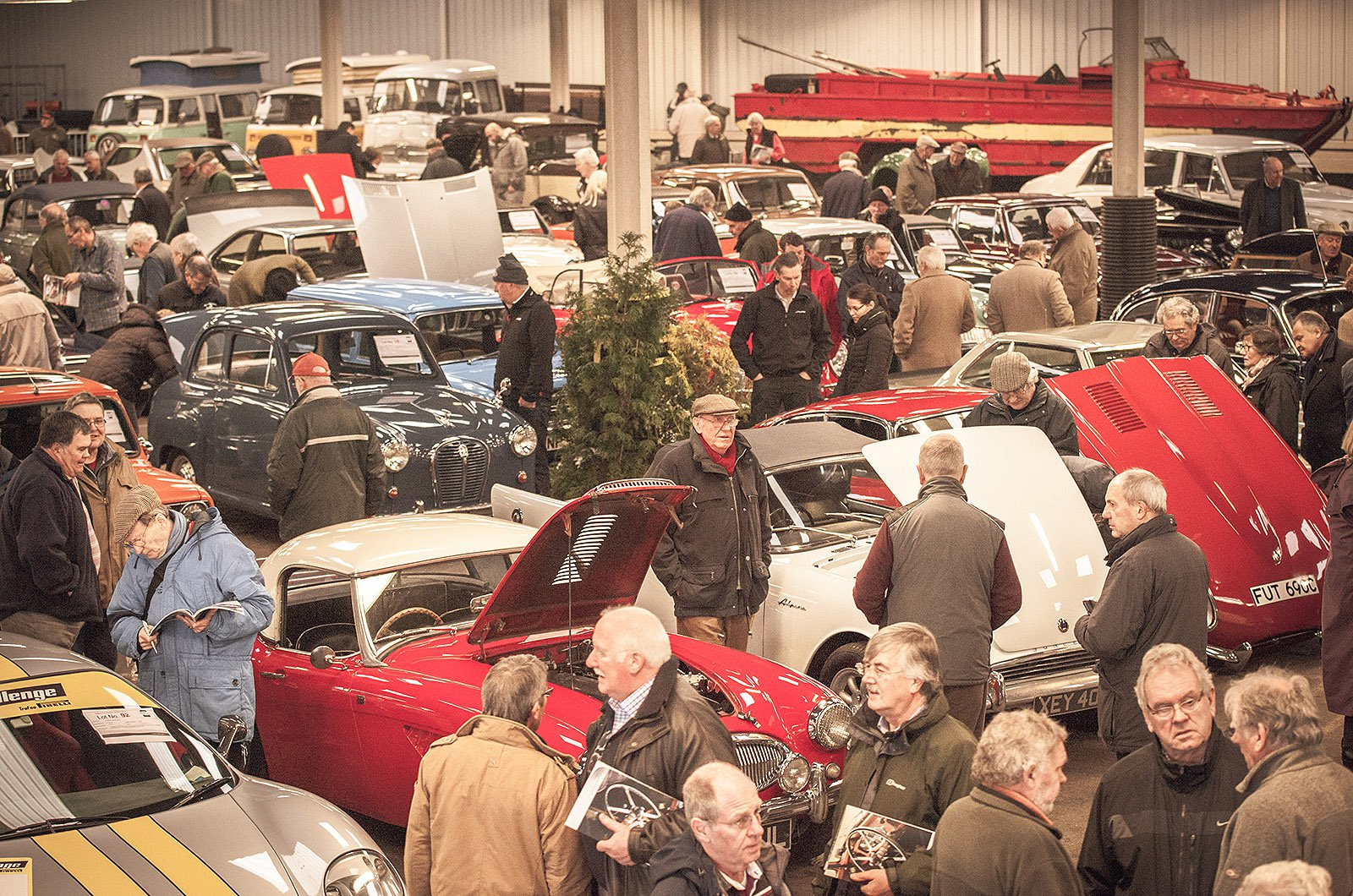 Potential bidders inspecting classic cars in warehouse before auction commences