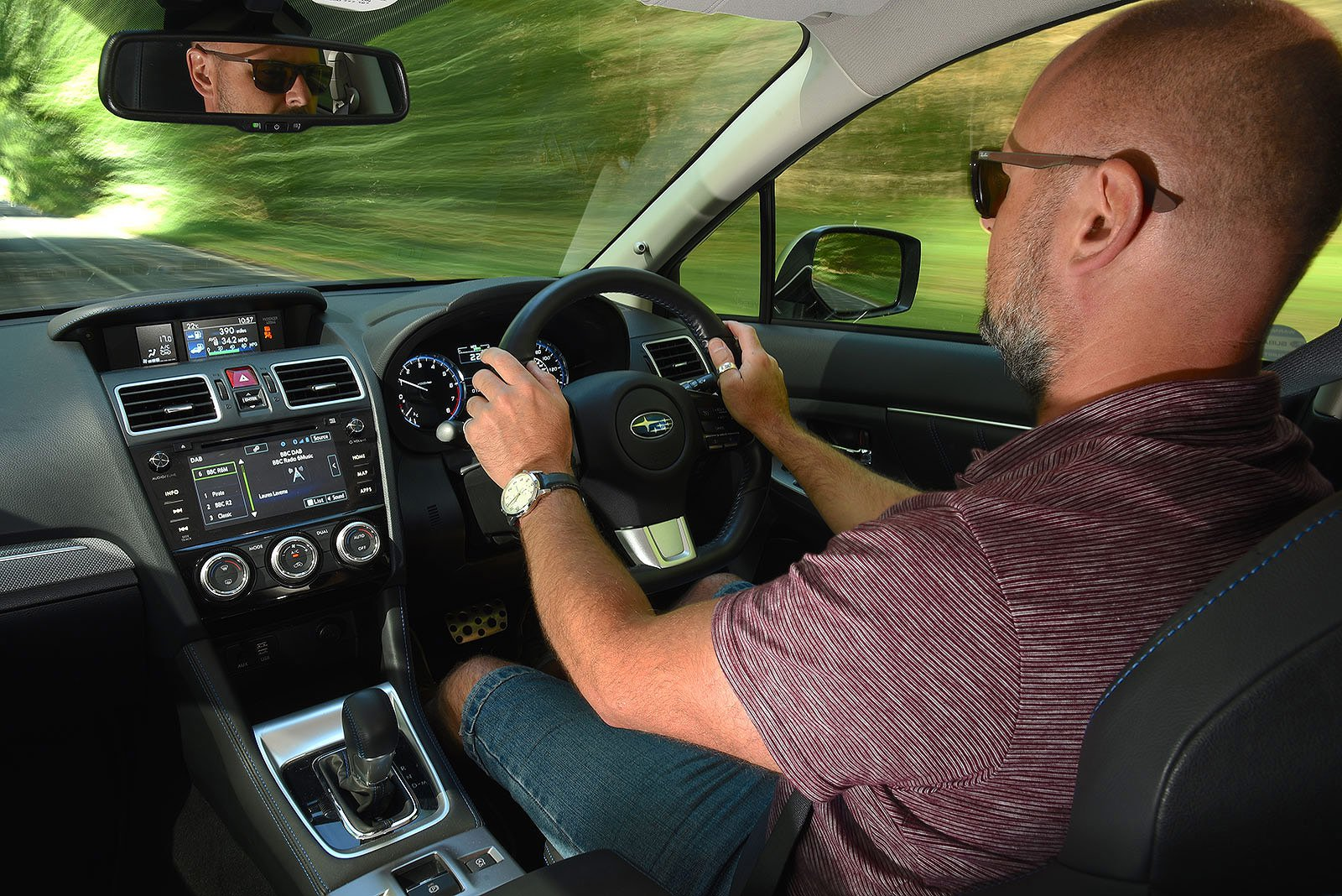 Over-the-shoulder shot of man driving a car
