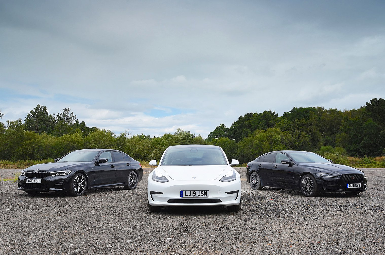 Tesla Model 3 parked with BMW 3 Series and Jaguar XE