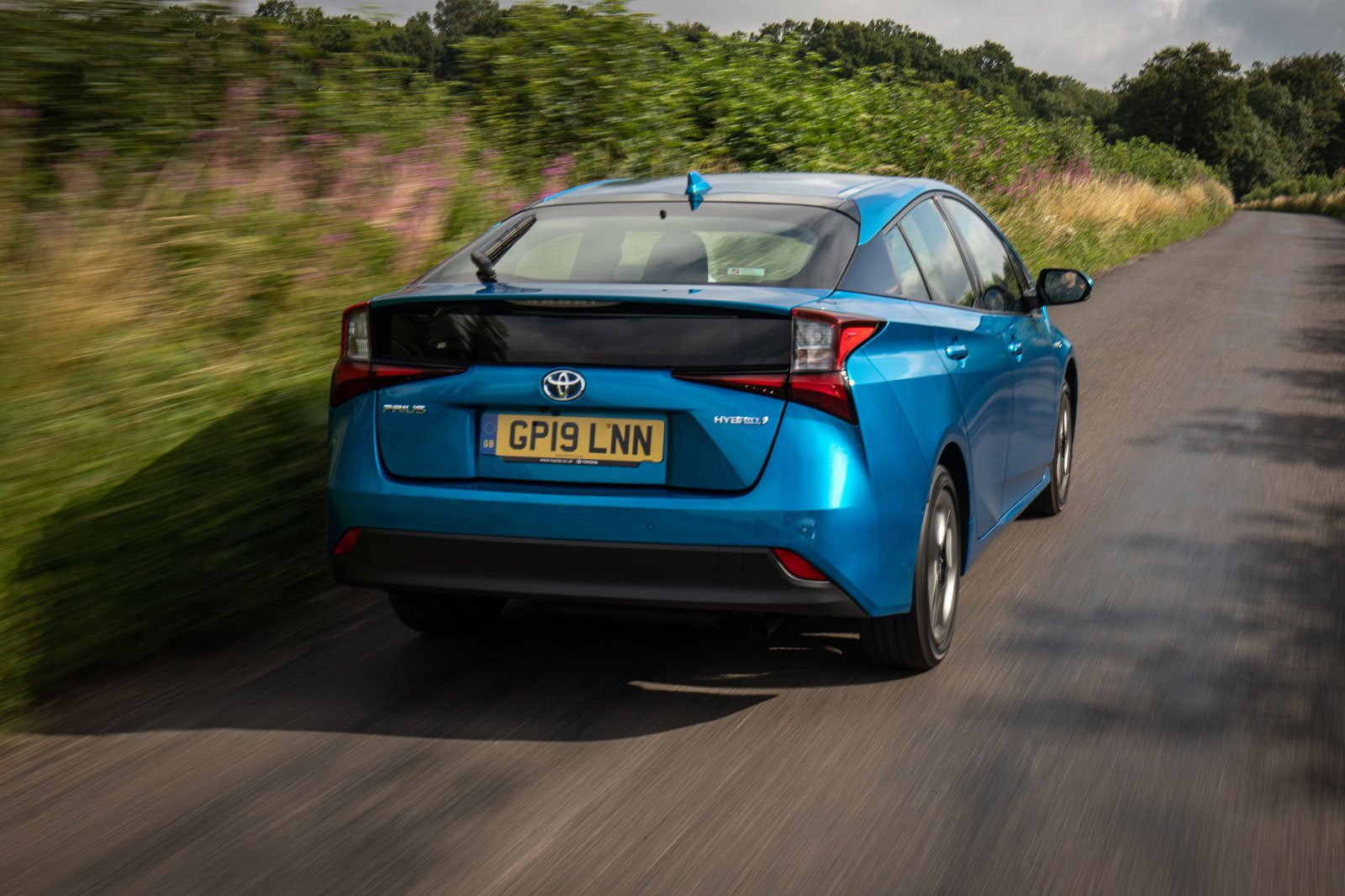2019 toyota prius awd blue driving rear