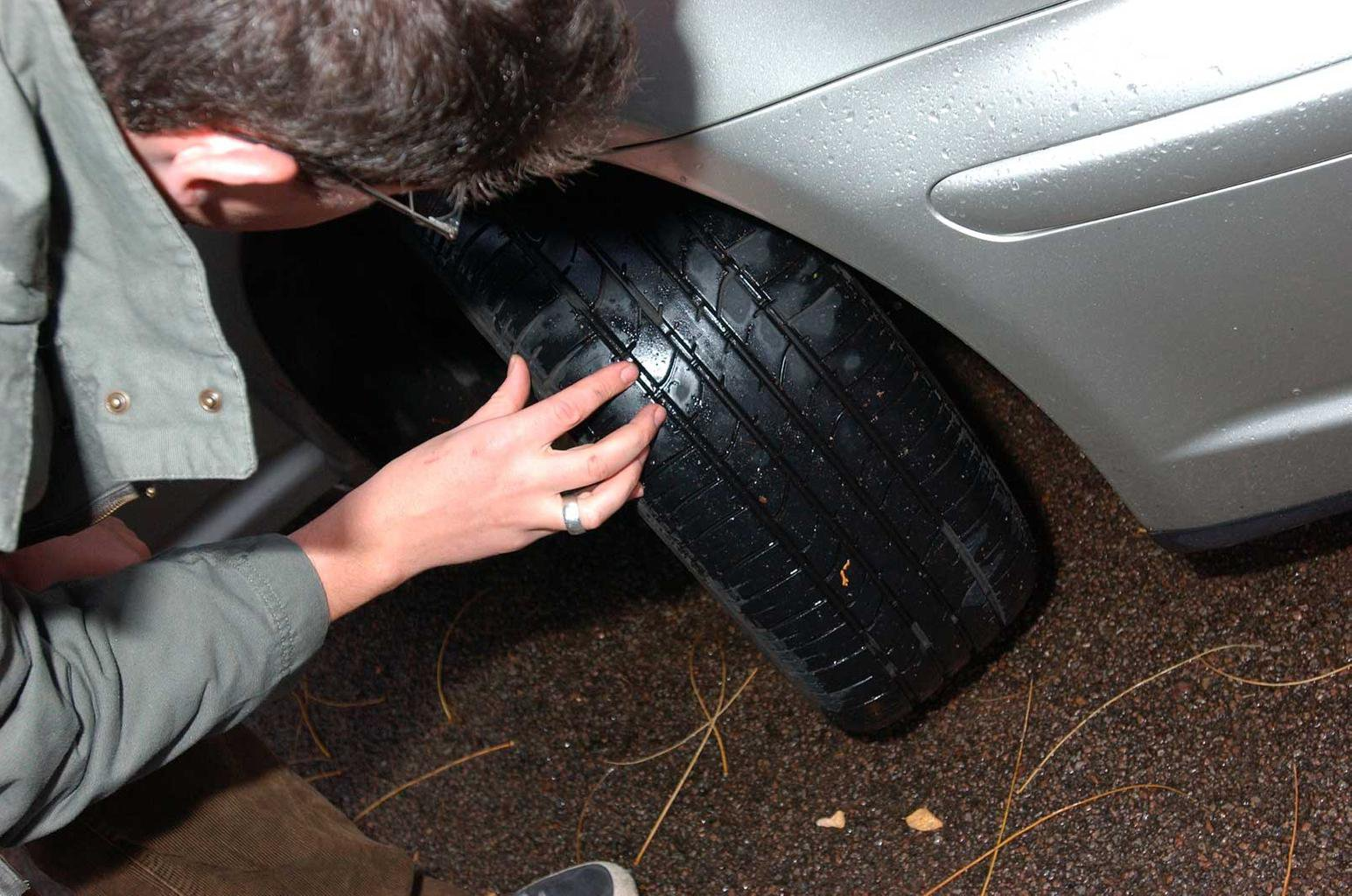 Man checking tyre tread depth