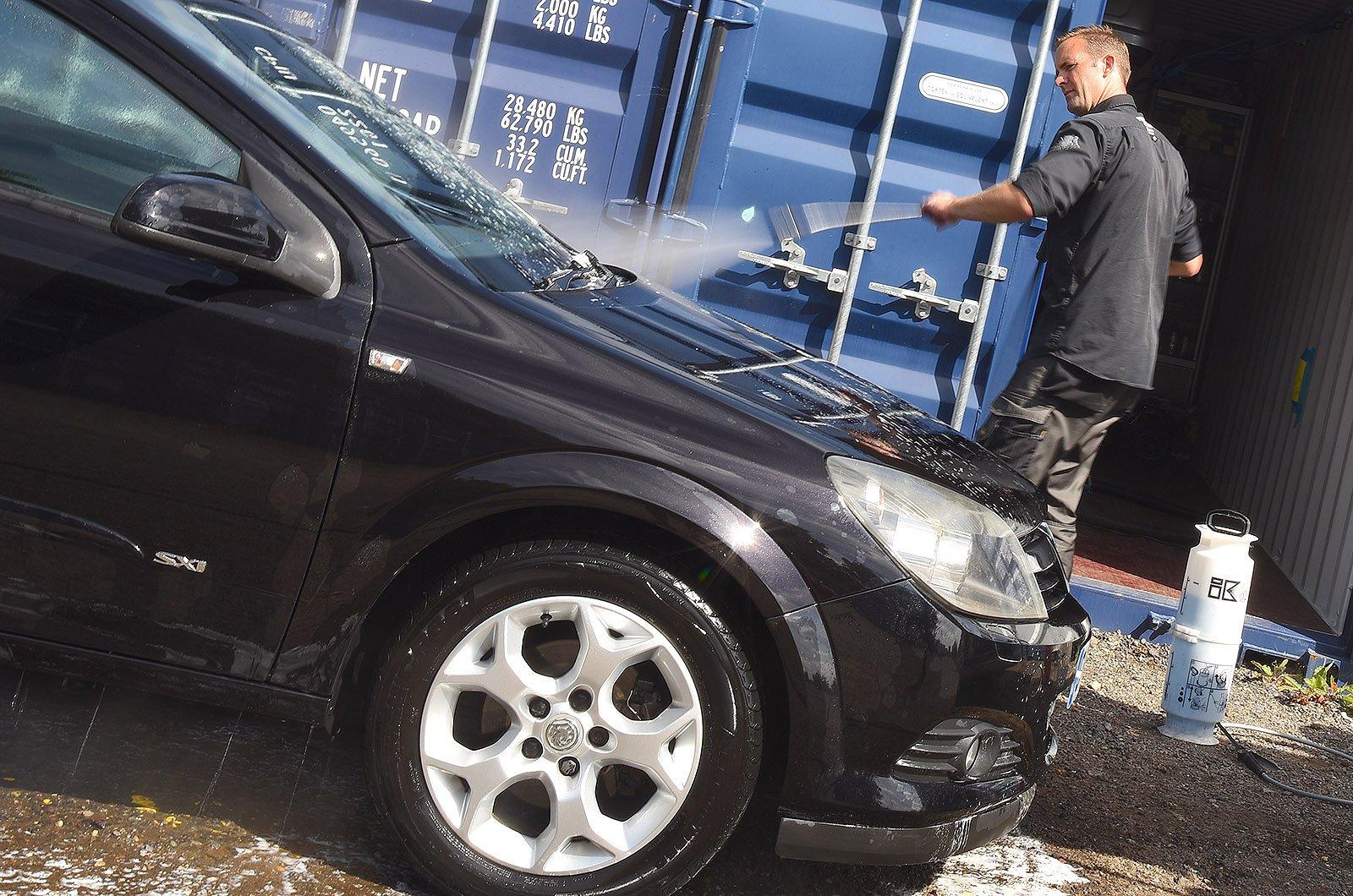 Car detailer rinsing an Astra
