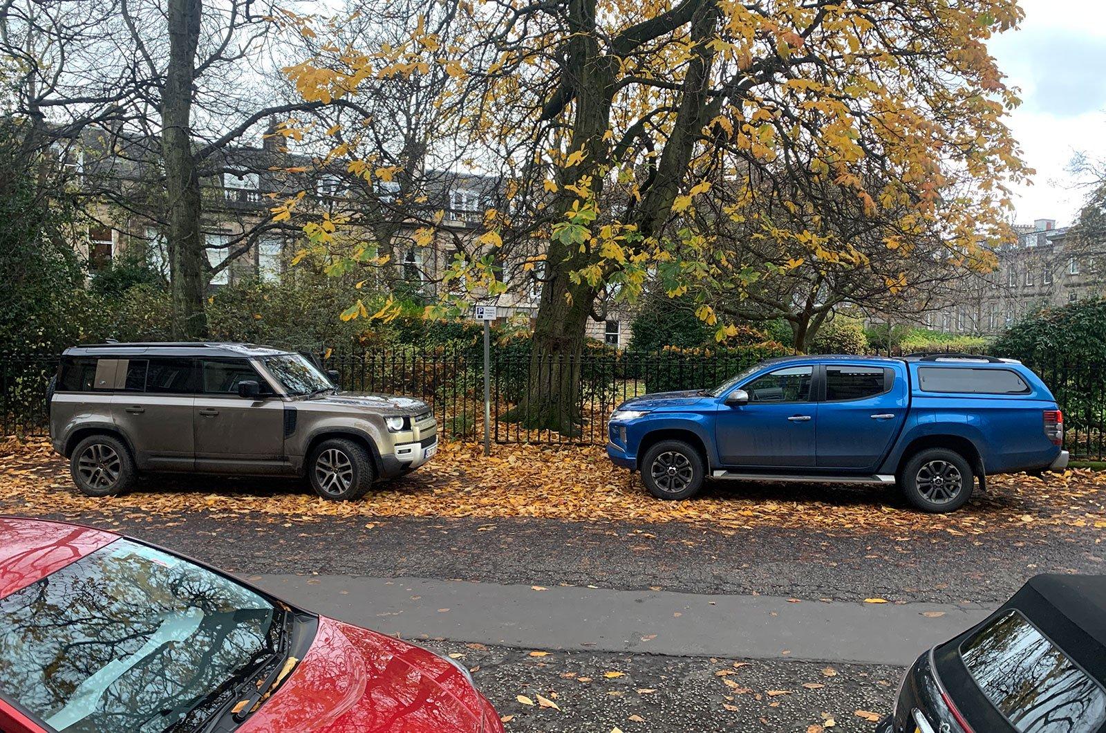Mitsubishi L200 next to Land Rover Defender