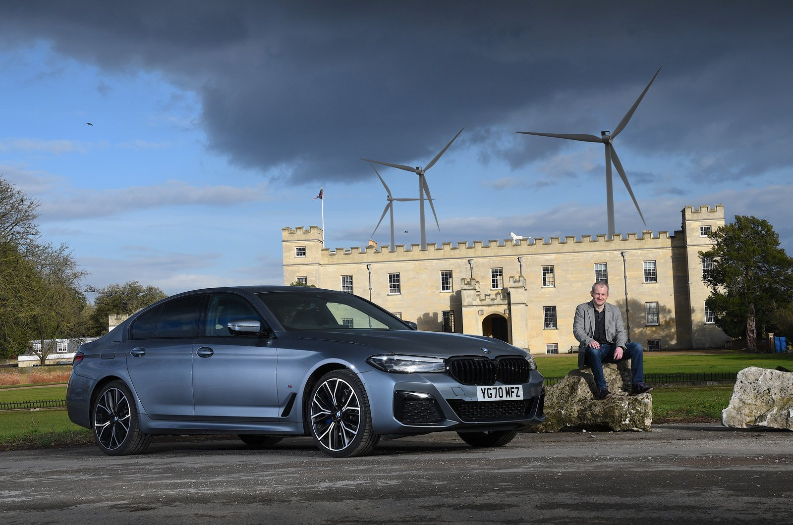 LT BMW 530e in front of stately home and wind turbines
